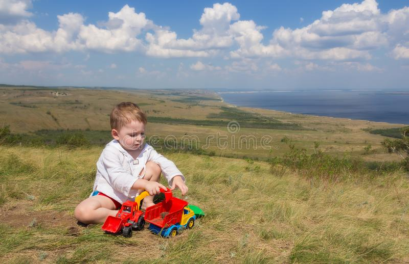 Little boy sitting on the grass and playing with cars on the background of a picturesque landscape overlooking the sea. stock photos