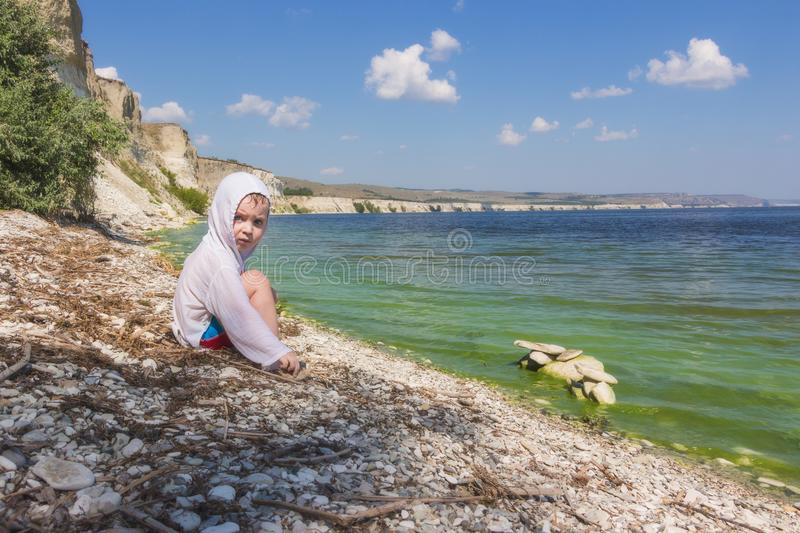 Little boy sitting on the seashore on the background of a picturesque landscape. stock image