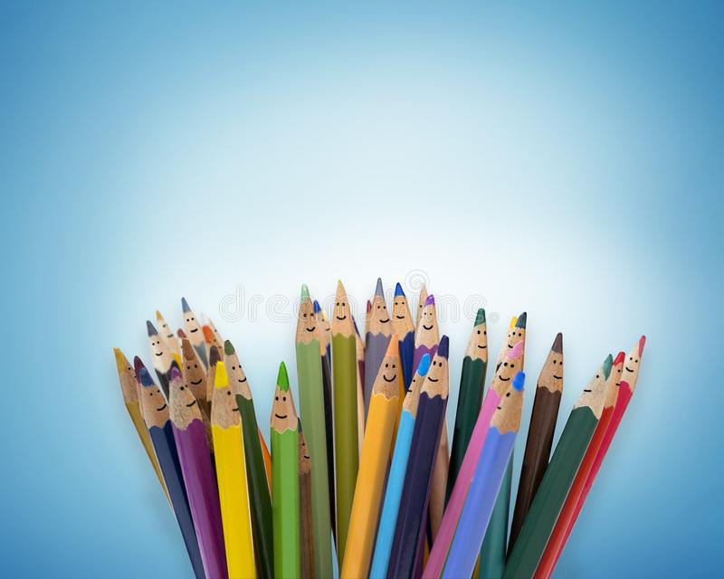 Colored pencils as faces of smiling children. Group of happy children. Concept of friendship and communication children. kindergar royalty free stock photo