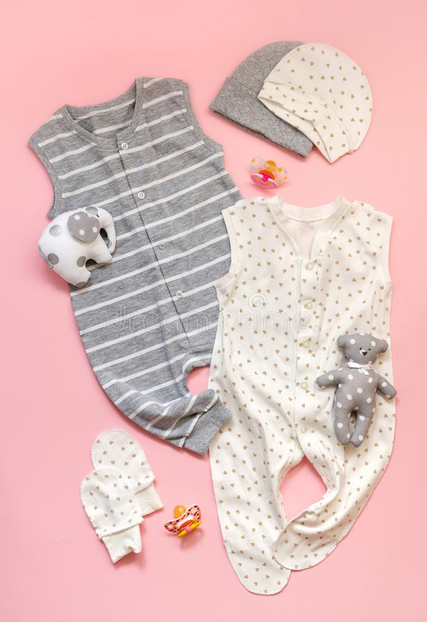 The concept of children`s clothing. set of white and gray children`s clothes on a light pink background. Sliders, toys, mittens. And dummy nipple. Fashionable stock photo