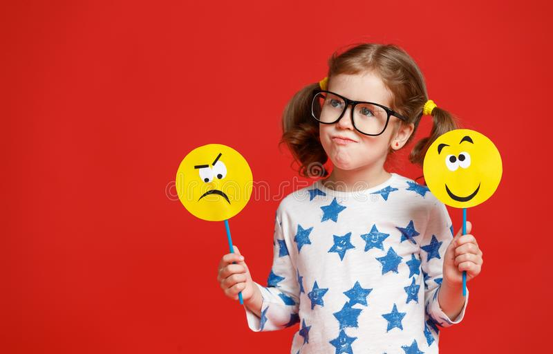 Concept of children`s emotions. child girl chooses between a sad royalty free stock image