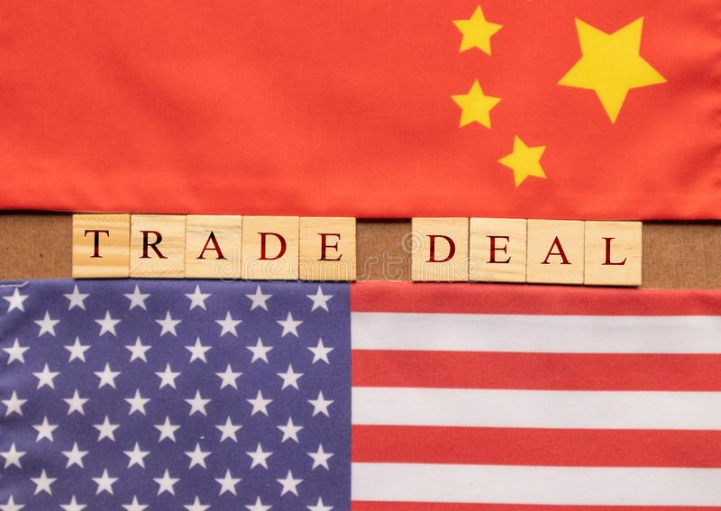 Concept of China US Trade deal, Trade Deal Printed on Wooden block letters in between China and US Flags stock photography