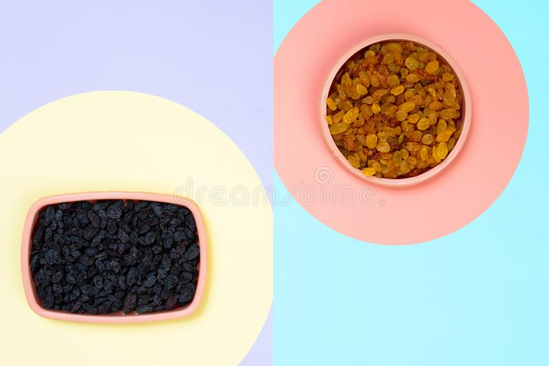 The concept of choosing food, right or bad. the concept of tasty and proper food. Minimalistic flat bark with plastic plates with yellow and black raisins on a stock image
