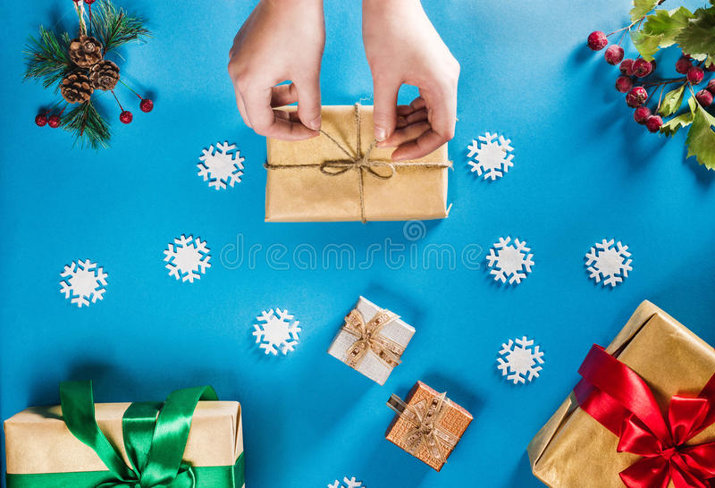 Concept of Christmas items on a bright blue background. Woman`s hands wrapping gift. Flat lay decorations, snowflakes stock image
