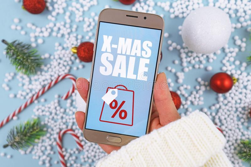 Concept for Christmas seasonal online shopping and sales wit hand holding cell phone with `X-Mas Sale` sign royalty free stock photo