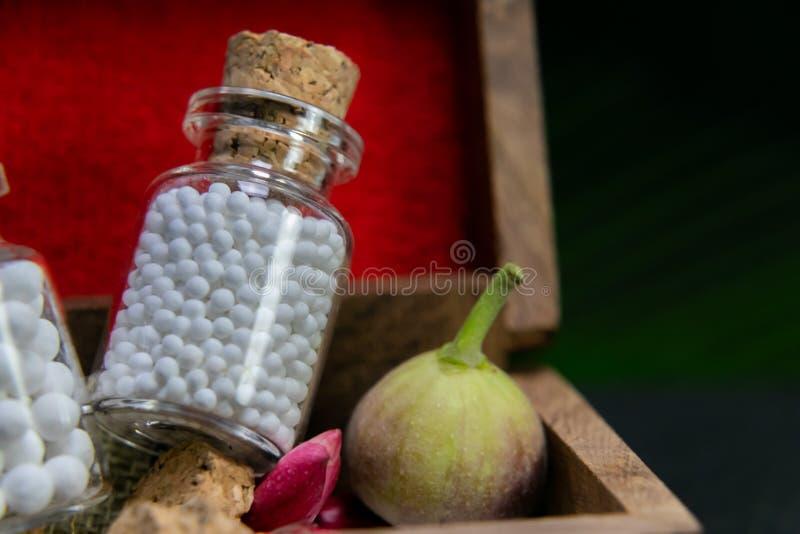 Concept classique d'homéopathie - fermez-vous des bouteilles de pilules homéopathiques avec le bourgeon floral sauvage, fruit sau photos libres de droits