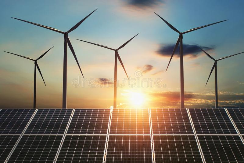 concept clean energy. wind turbine and solar panel in sunris royalty free stock image