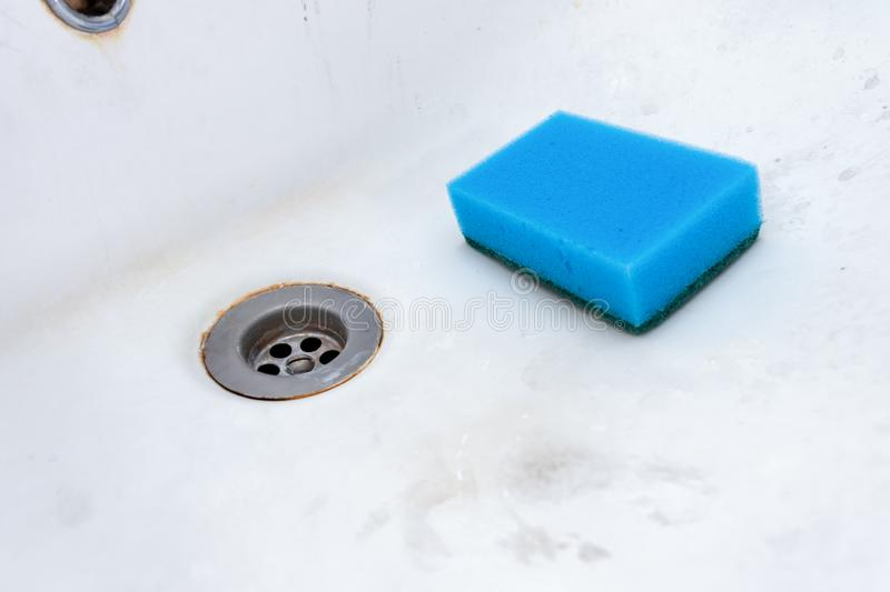 Concept of cleaning old dirty washbasin with rust stains, limescale and soap stains in the bathroom.  royalty free stock photography