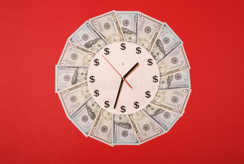 Concept of clock and dollar. Clock on mandala kaleidoscope from money. Abstract money background raster pattern repeat mandala. Circle. On red background stock photo