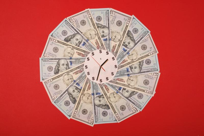 Concept of clock and dollar. Clock on mandala kaleidoscope from money. Abstract money background raster pattern repeat mandala. Circle. On red background stock photography