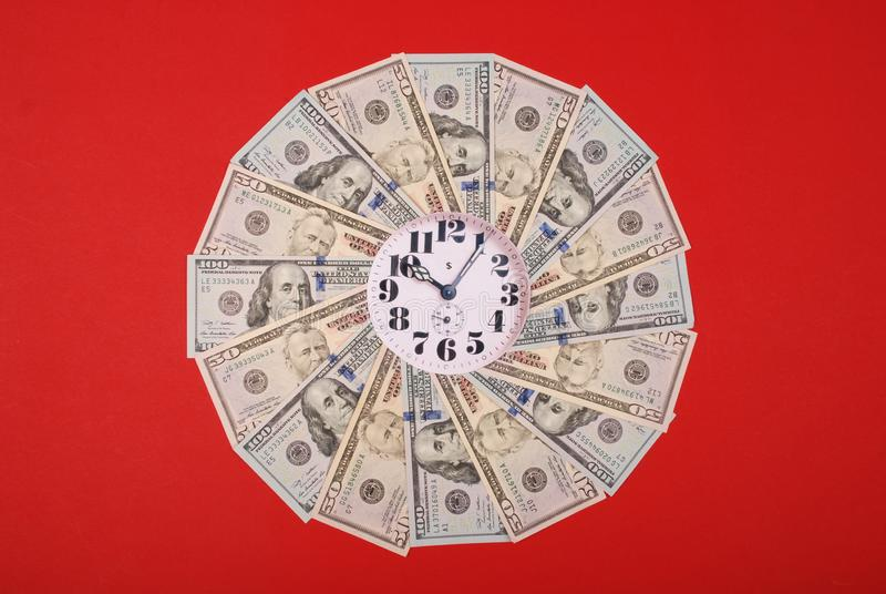 Concept of clock and dollar. Clock on mandala kaleidoscope from money. Abstract money background raster pattern repeat mandala. Circle. On red background royalty free stock image