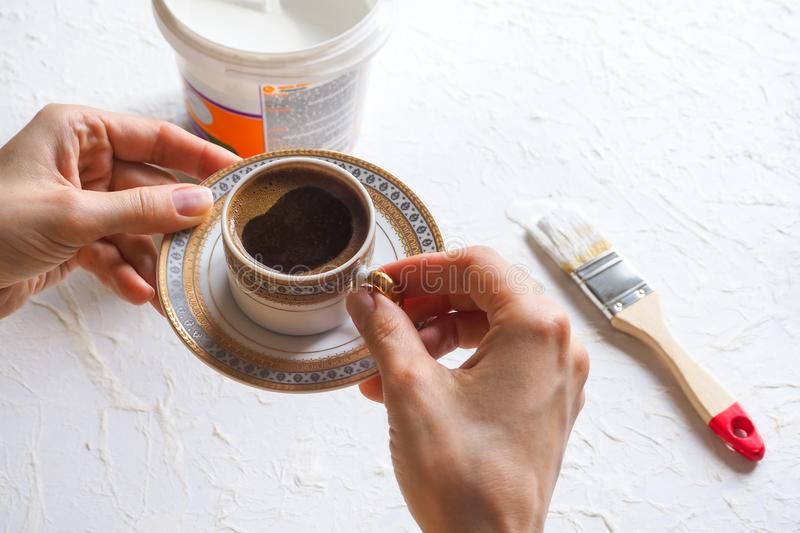 The concept of the coffee break in the workplace. A Cup of coffee in the hands of the painter. royalty free stock photography