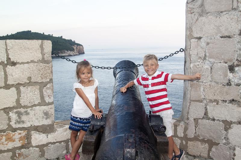 Concept of cognitive recreation with children. happy and smiling boy with a girl standing near an old cannon on the city wall. Enclosing the old town of stock image