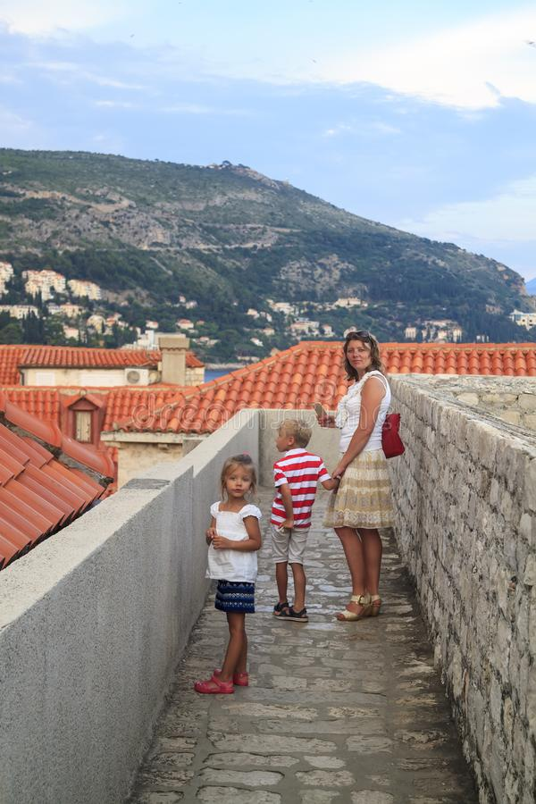 Concept of cognitive recreation with children. traveling mother, daughter and son on the walls enclosing the old town of Dubrovnik. At sunset, croatia, view royalty free stock photo