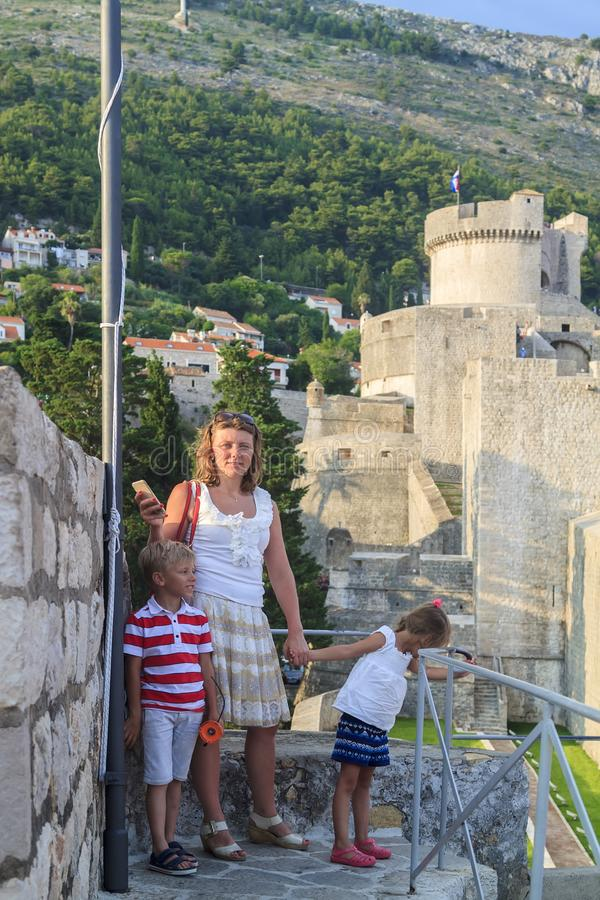 Concept of cognitive recreation with children. traveling mother, daughter and son on the walls enclosing the old town of Dubrovnik. At sunset, croatia, view royalty free stock images