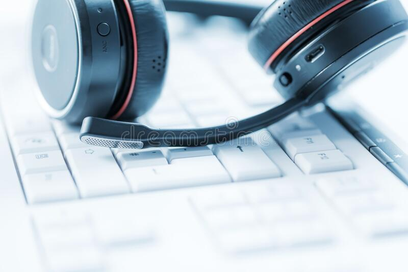 Concept of communication support, call center and customer service help desk. Headphones on keyboard royalty free stock image