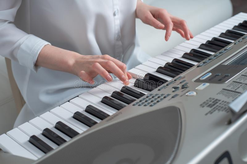 The concept of composing melodies, hands playing the synthesizer.  stock image