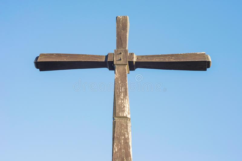 Concept or conceptual wood cross or religion symbol shape over a blue sky. Simple wooden Christian cross against a blue sky.  royalty free stock images