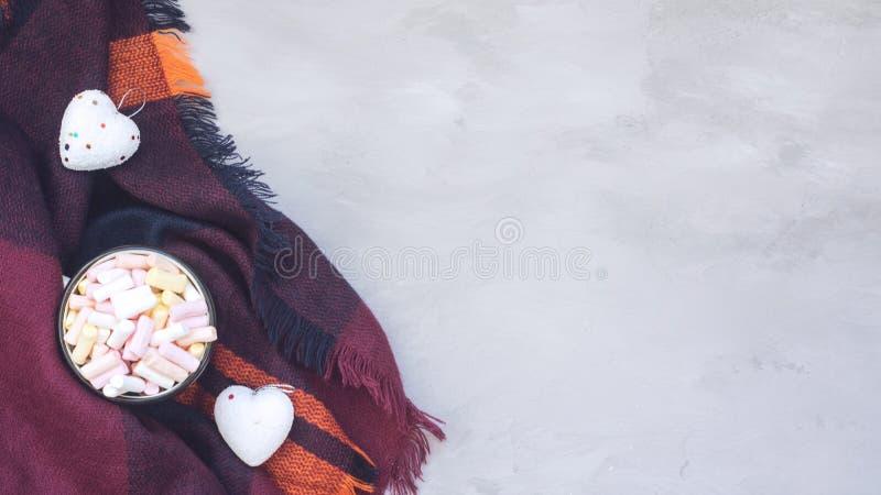 Concept confortable d'hiver, bannière, maquette Café avec des guimauves dans la tasse émaux et des coeurs blancs décoratifs sur l photographie stock