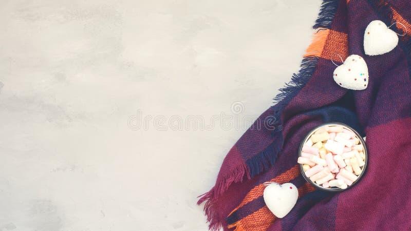 Concept confortable d'hiver, bannière, maquette Café avec des guimauves dans la tasse émaux et des coeurs blancs décoratifs sur l image libre de droits