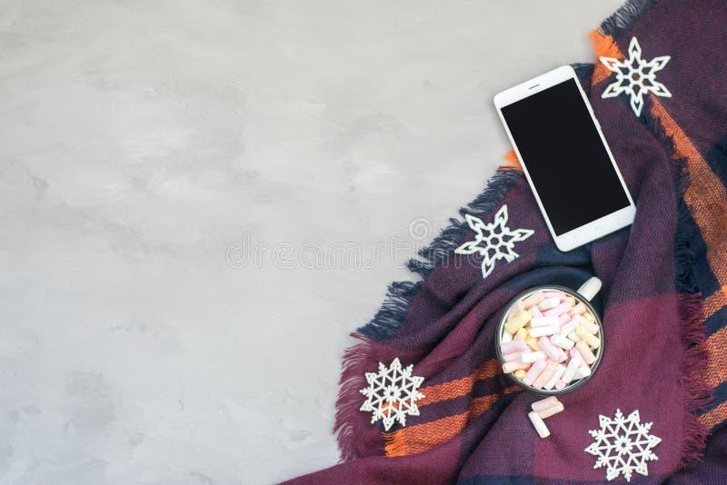 Concept confortable d'hiver, bannière, maquette Café avec des guimauves en tasse émaux blanche, smartphone et flocon de neige bri images stock