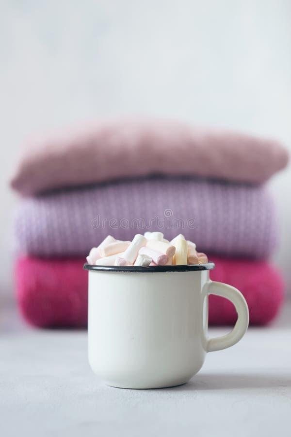 Concept confortable d'hiver Temps de chandail Café avec des guimauves dans la tasse émaux blanche en métal sur le fond de la pile photo stock