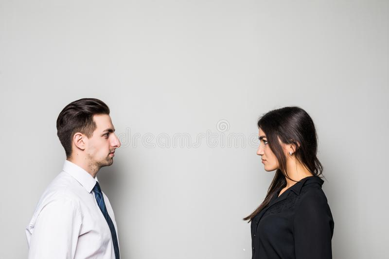 Concept of confrontation in business. Close up photo of two young serious confident people standing face-to-face to each other on. Concept of confrontation in royalty free stock photography