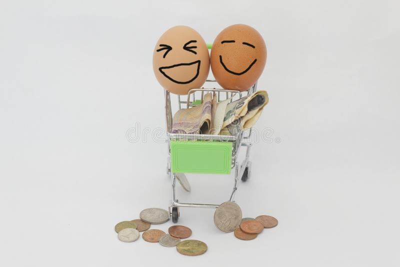 Concept consumentisme en het winkelen Gelukkig gezicht met geld en boodschappenwagentje op geïsoleerde witte achtergrond stock afbeeldingen