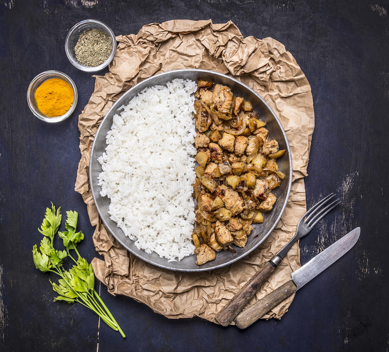 Concept Cooked turkey recipe Thai fried rice should be half the pan on paper seasoned greens fork knife dark blue rustic wo stock image