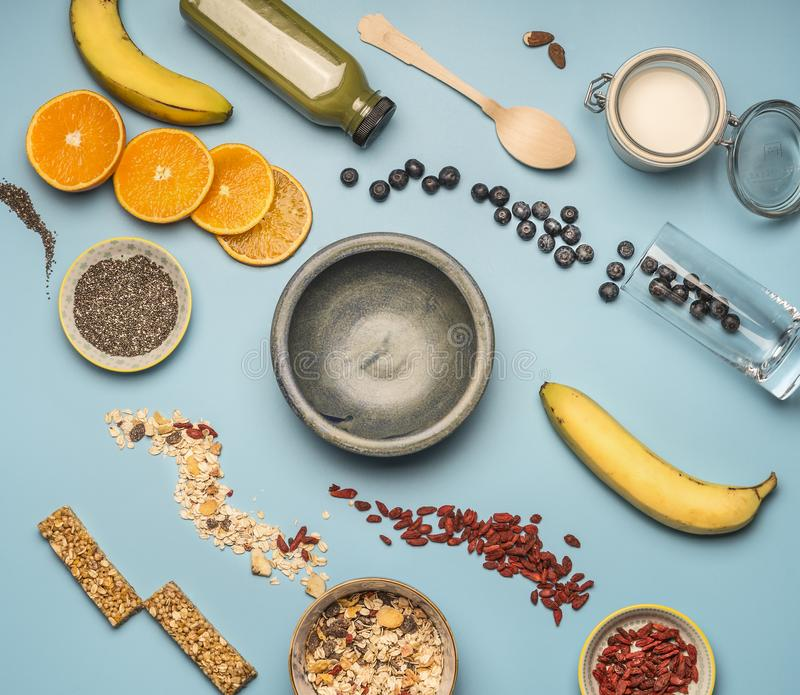 Concept of cooking a healthy breakfast, berries, bananas, oranges, cereals, and milk, a vintage bowl on a blue background flat lay. Concept of cooking a healthy royalty free stock photos