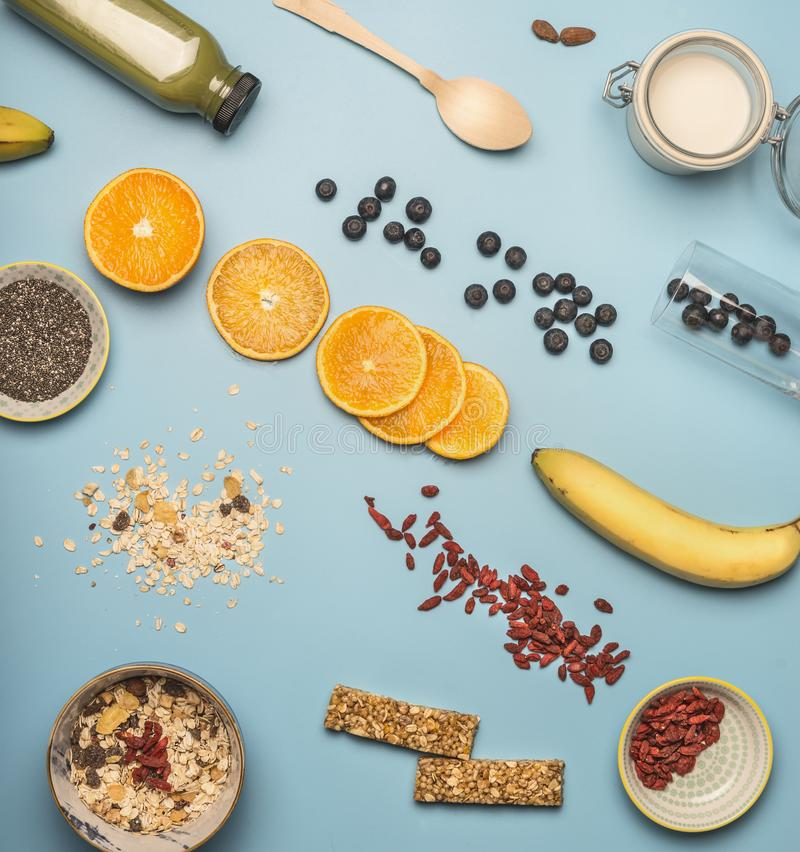 Concept of cooking a healthy breakfast, berries, bananas, oranges, cereals, nutritious bars and milk, a vintage bowl on a blue bac. Concept of cooking healthy stock images