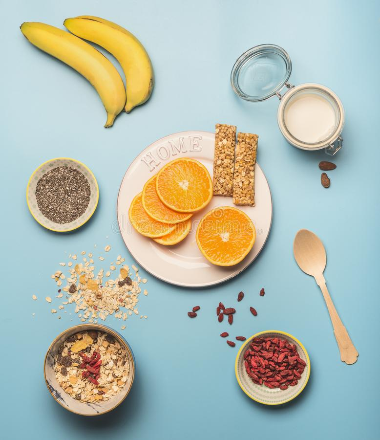 Concept of cooking healthy breakfast, berries, bananas, smoothies, blueberries, oranges, cereals, nutritious bars and milk, a vint stock photography
