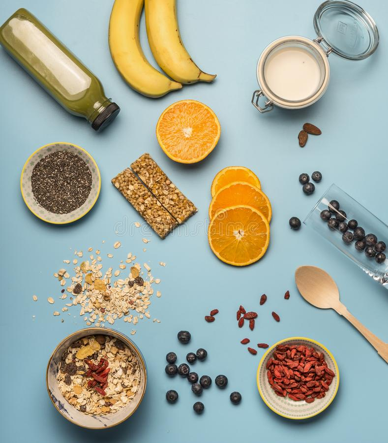 Concept of cooking healthy breakfast, berries, bananas, smoothies, blueberries, oranges, cereals, nutritious bars and milk, a vint stock image