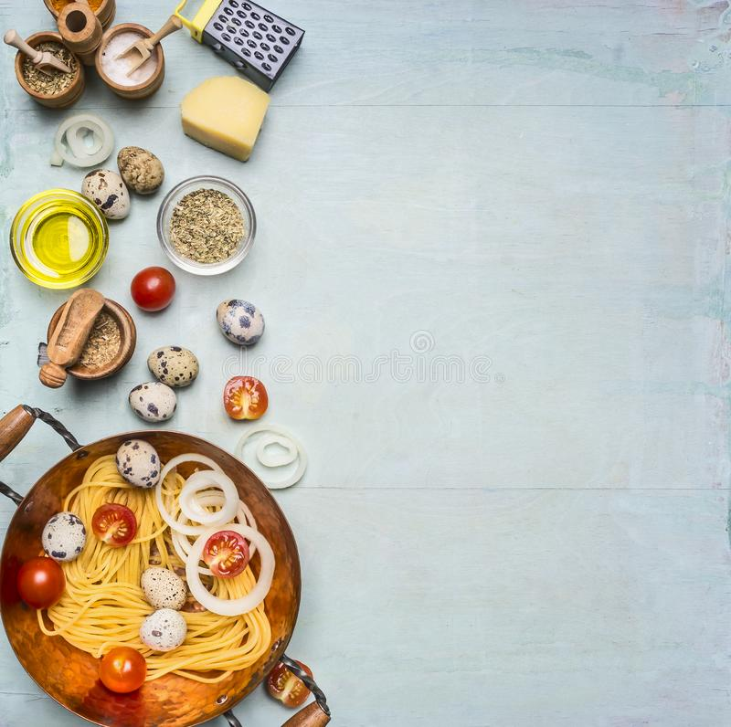 Concept cooking homemade vegetarian pasta with cherry tomatoes, parmesan cheese, quail eggs and seasonings, pasta in copper bowl royalty free stock images