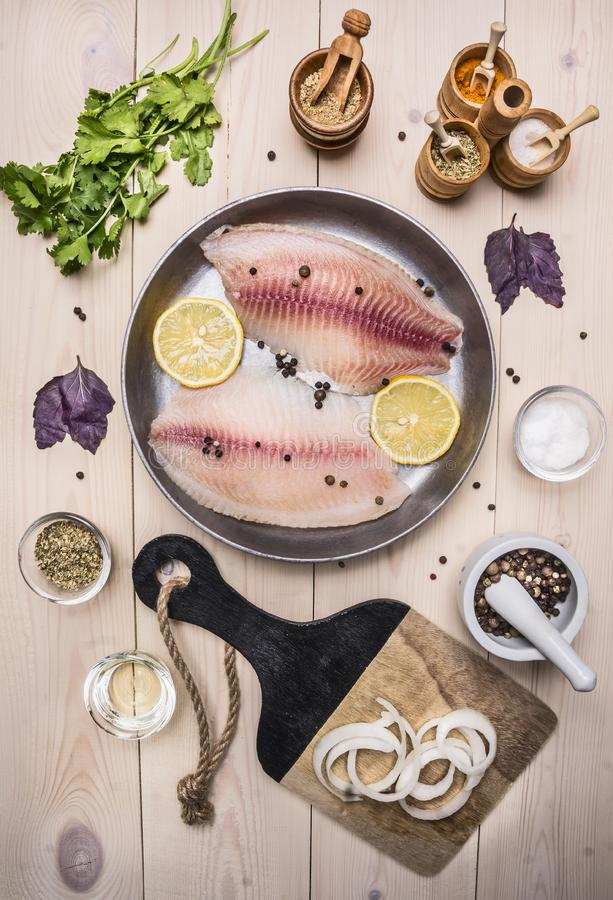 Concept cooking tilapia fillets with lemon a vintage pan with herbs, vegetables and spices on wooden rustic background top view stock images