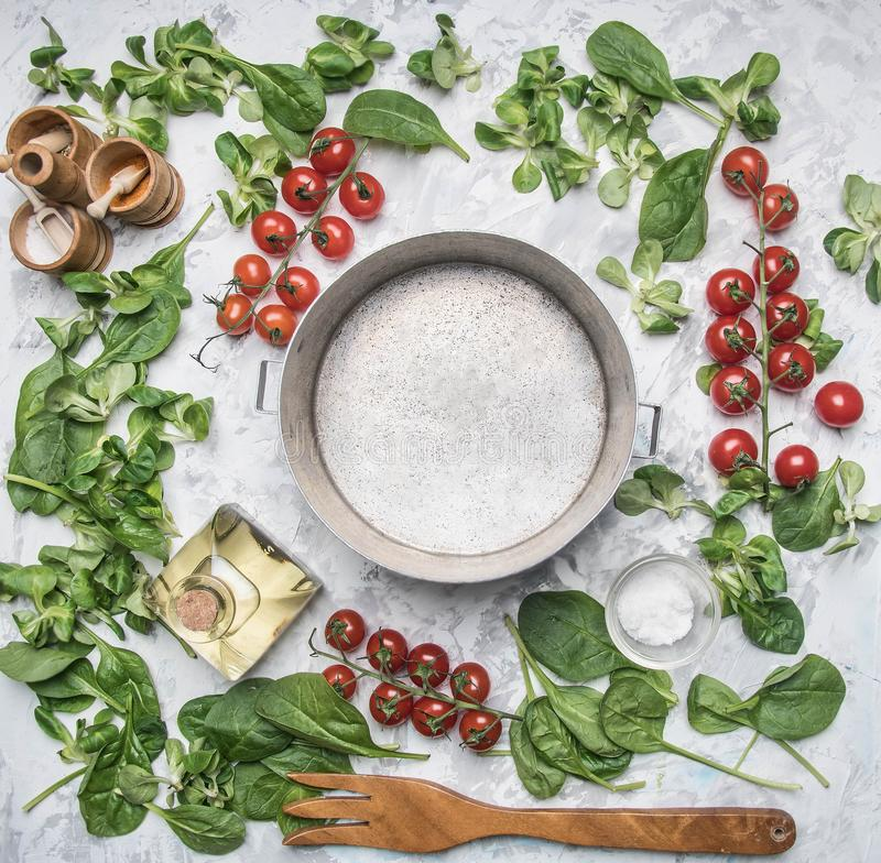 Concept of cooking vegetarian food, cherry tomatoes, various salad varieties, seasonings, spices, olive , lined around the vint stock photo