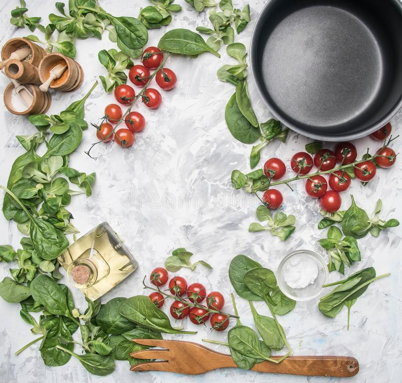 Concept of cooking vegetarian food, cherry tomatoes, various salad varieties, seasonings, spices, olive , and a pan, lined with royalty free stock images