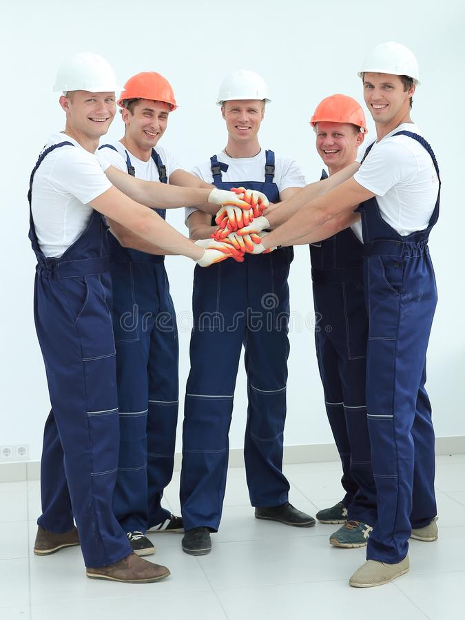 Team of builders standing with hands clasped together stock image