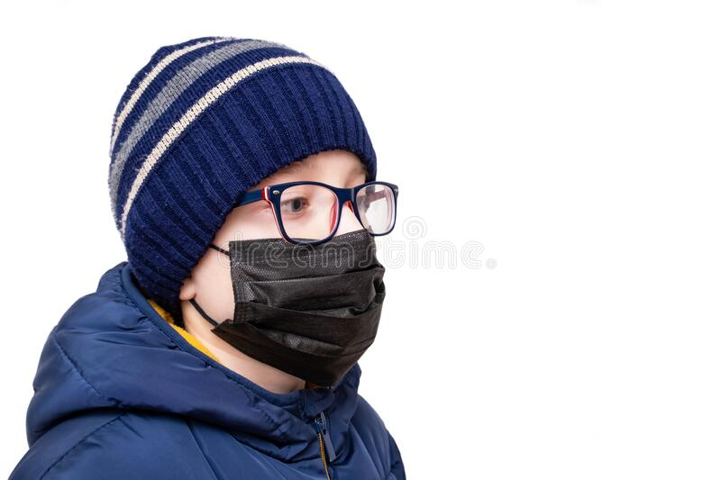 Concept of coronavirus quarantine. A boy in winter clothes and a black respiratory medical surgical mask as a protection from. Viruses and bacteria royalty free stock photos