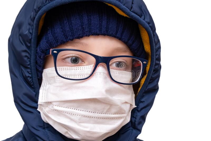 Concept of coronavirus quarantine. A boy in winter clothes and a white respiratory medical surgical mask as a protection from. Viruses and bacteria royalty free stock photos
