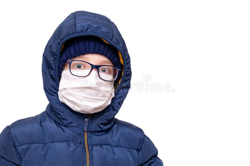Concept of coronavirus quarantine. A boy in winter clothes and a white respiratory medical surgical mask as a protection from. Viruses and bacteria royalty free stock photography