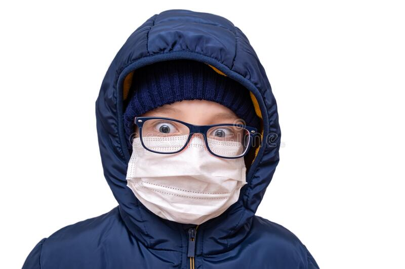 Concept of coronavirus quarantine. A boy in winter clothes and a white respiratory medical surgical mask as a protection from. Viruses and bacteria royalty free stock photo