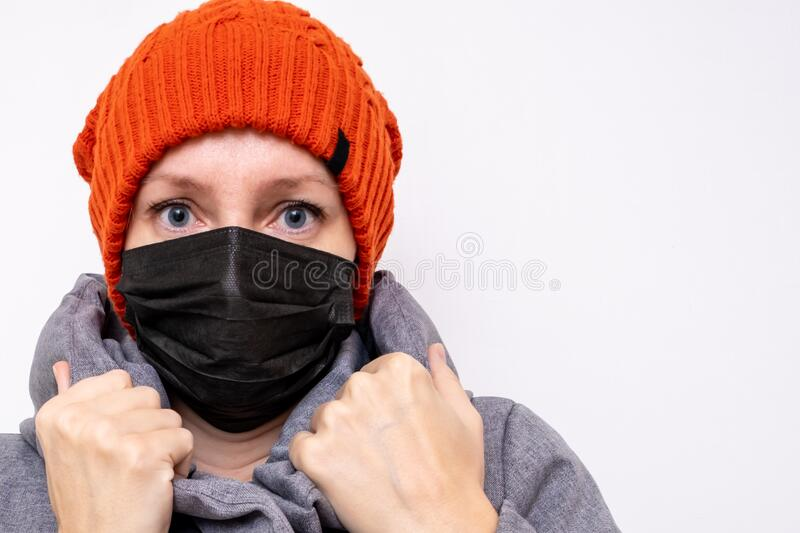 Concept of coronavirus quarantine. Woman in winter clothes and a black respiratory medical surgical mask as a protection from. Viruses and bacteria stock photo