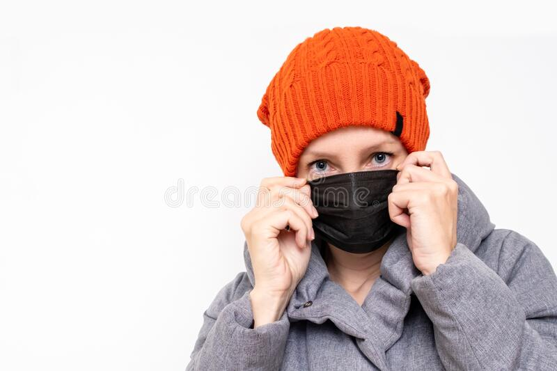 Concept of coronavirus quarantine. Woman in winter clothes and a black respiratory medical surgical mask as a protection from. Viruses and bacteria royalty free stock image