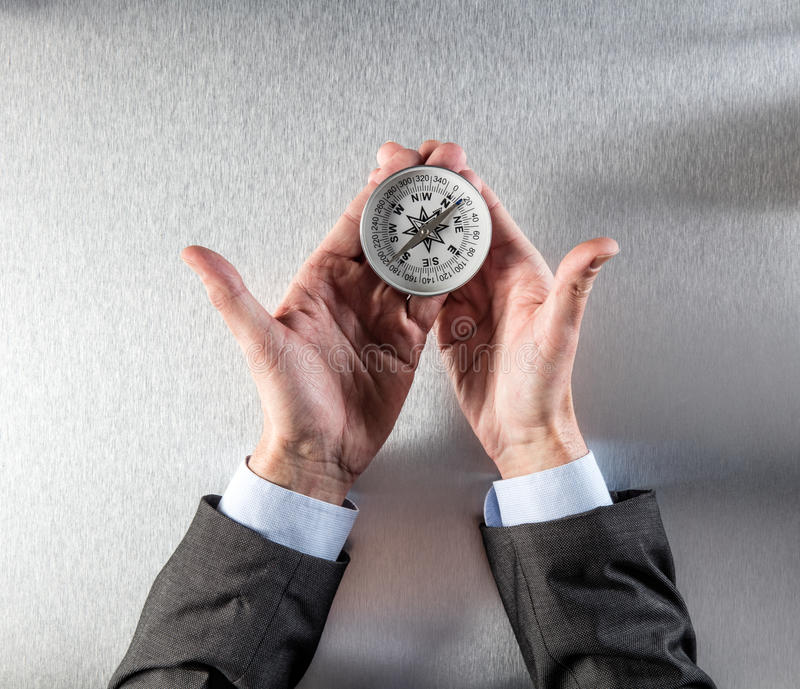 Concept of corporate exploration for businessman hands holding a compass royalty free stock photography