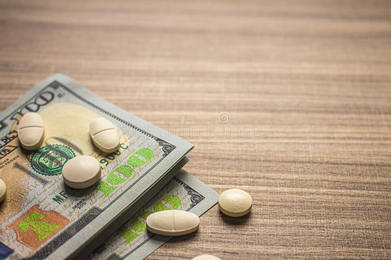 Concept of cost of medicines. Several Pills on a brown table with bills stock image