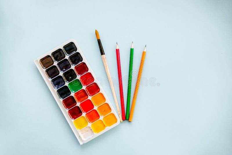 Concept créatif, aquarelles avec une brosse et crayons sur le fond bleu-clair images stock