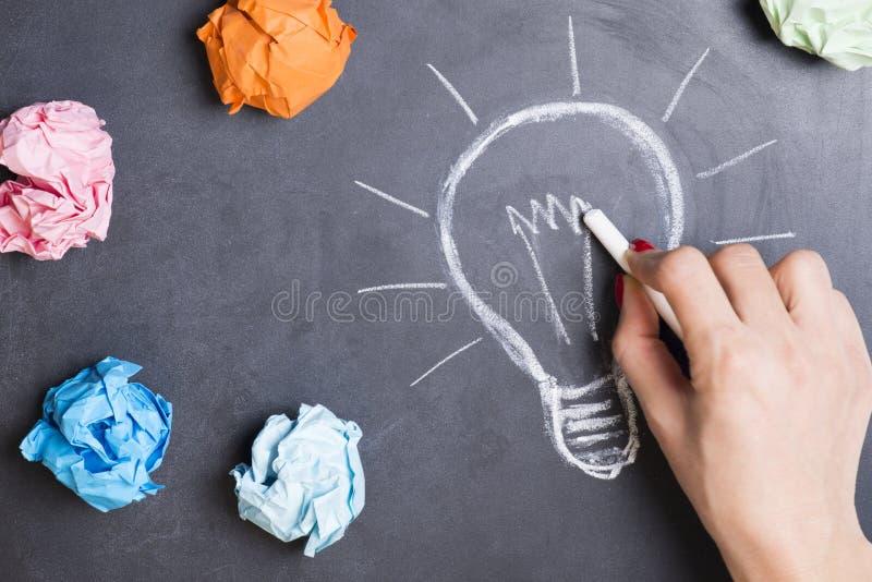 Concept cr?atif d'id?e avec la main de femme dessinant l'ampoule avec la craie sur le tableau noir image stock