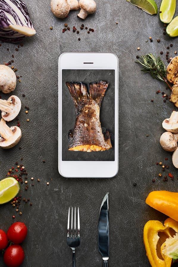 Concept créatif de nourriture avec la queue rôtie de poissons dans l'affichage de smartphone Concept de la livraison de restauran photos libres de droits