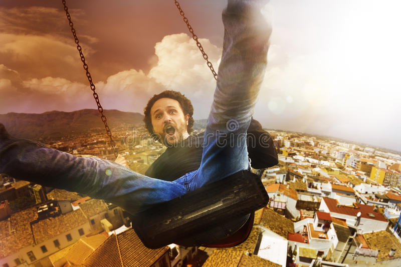 Concept crazy, mad and happy man climbed a swing stock photo